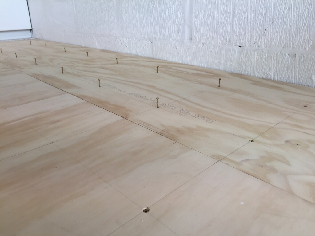 """Screws at 18"""" intervals on second layer of the gym floor"""